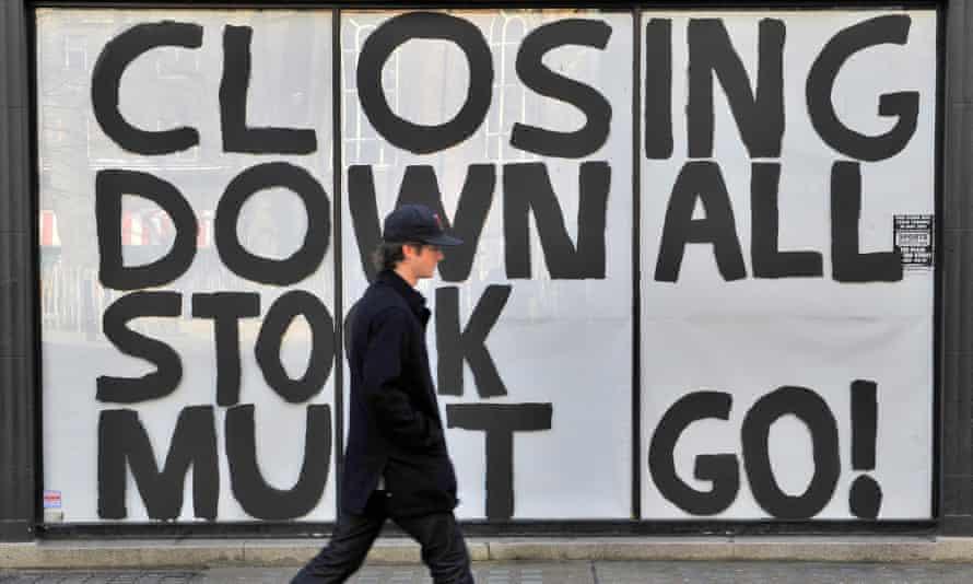 Man walking past closing down sign
