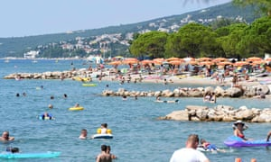 CROATIA-HEALTH-VIRUS-TOURISMPeople, mostly foreign tourists, sunbath and swim on 13 August, 2020, in Crikvenica on the northern Adriatic coast. (Photo by DENIS LOVROVIC/AFP via Getty Images)