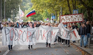 Protesters hold a banner during a rally against Covid-19 restrictions in Ljubljana on October 5, 2021.