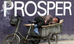 A man takes a nap under a billboard saying 'prosper' in Beijing