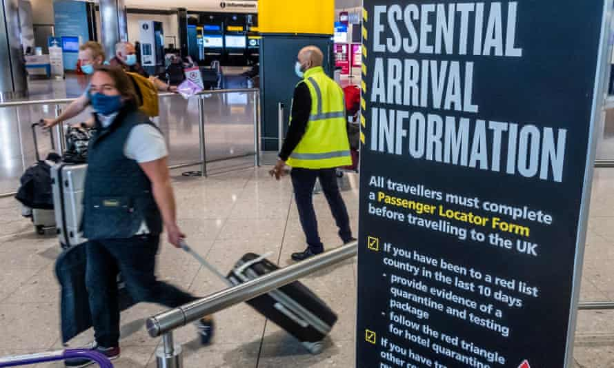 Passengers heading for quarantine at Heathrow are escorted by staff.