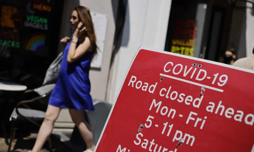 A pedestrian walks past a Covid road sign in London