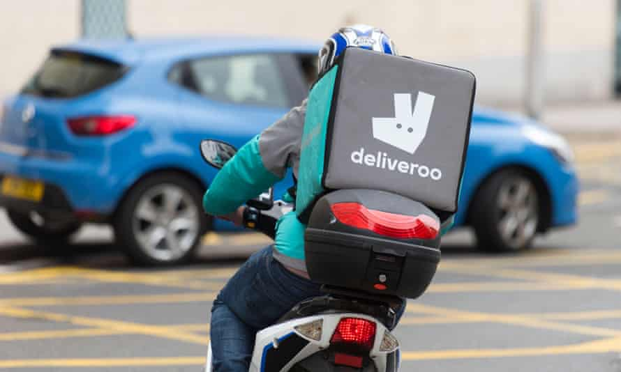 A Deliveroo rider on a moped making a food delivery