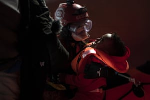 A baby is rescued by aid workers from the Spanish NGO Open Arms, after being located sailing adrift on an overcrowded wooden boat in the Mediterranean about 85 miles north of Libya.