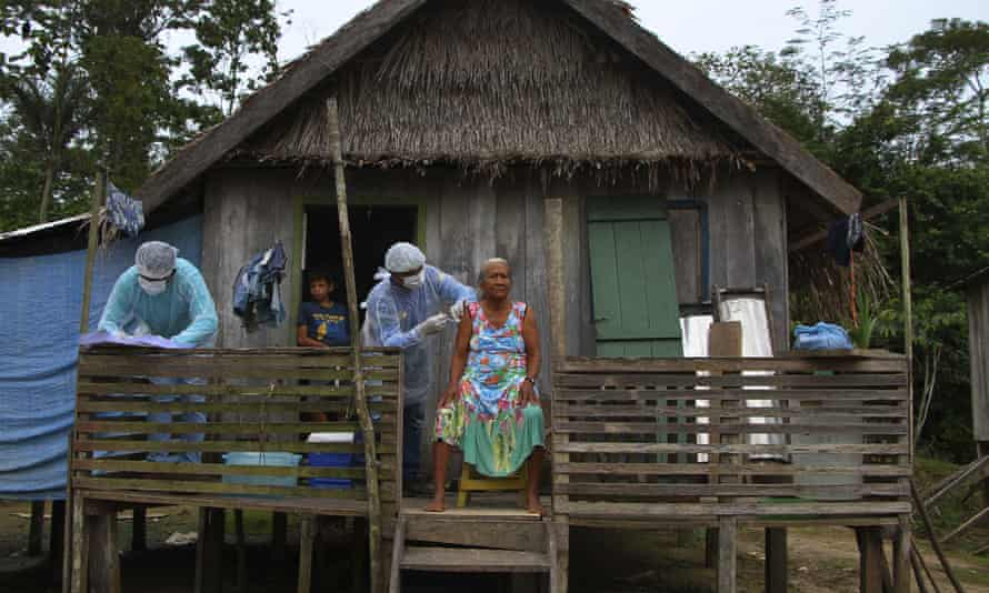A woman receives a dose of the Oxford/AstraZeneca Covid-19 vaccine on the porch of her home in Amazonas state, Brazil.