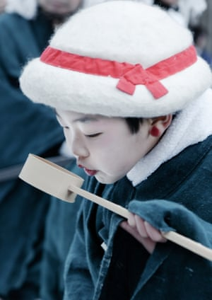 A child performing the Tori-mai purification ritual drinks water from a traditional chōzuya