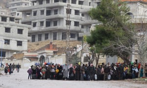 Residents of the besieged rebel-held Syrian town of Madaya wait for a convoy of aid from the Syrian Arab Red Crescent on 14 January.