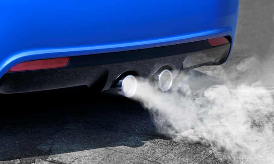Exhaust is seen coming out of twin exhaust pipes on a car