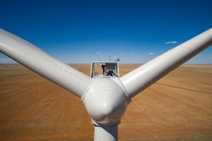Two wind technicians secure themselves to the top of a wind turbine during annual inspection of the Roosevelt wind farm in eastern New Mexico.