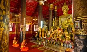Monks praying before golden Buddha inside Wat Mai temple.