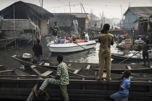The picture shows a boat with tourists from Lagos Marina, steered through the canals of the Makoko community - an ancient fishing village that has grown into an enormous informal settlement on the shores of Lagos lagoon.