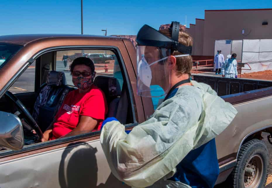 A nurse takes a swab sample from a Navajo Indian woman complaining of virus symptoms, at a testing center at the Navajo Nation town of Monument Valley in Arizona on 21 May.