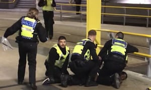 Police restraining Mahdi Mohamud after three people were stabbed at Victoria station, in Manchester, on New Year's Eve.