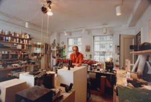 man in orange shirt in room lit by a spotlights and crammed with artist paraphernalia