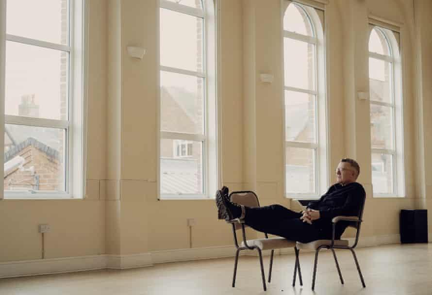 Tom Watson sitting in an empty room with large windows