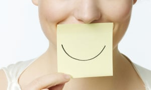 A woman smiling holding a Post-it note with a smile drawn on it.