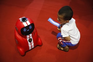 Beijing, China A child holding an entrance ticket watches a self-learning robot during the World Robot Conference at the Yichuang International Conference and Exhibition Centre