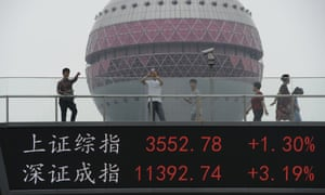 People walk on a footbridge with an electronic stock ticker showing real time stock market indices in Shanghai, China on 9 July.