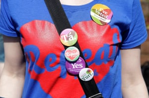 A woman wears a campaign T-shirt and badges