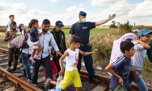A policeman directs refugees at Röszke crossing on Serbian-Hungarian border.
