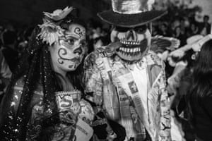 Women have their faces painted with the distinctive 'La Catrina' design, emblematic of the Day of the Dead festival, and wear flowers in their hair.