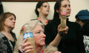 Flint residents, including Jessica Owens, right, holding a baby bottle full of contaminated water, are seen during a news conference in Washington DC. Williamson, and Owens traveled to Washington by bus with other Flint families to attend the House hearing on the crisis.