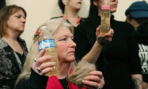 Flint residents hold bottles full of contaminated water.