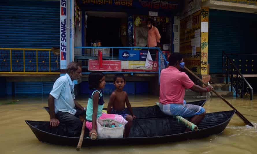 People living along the Shilabati River in Bengal, India, navigate their town by boat after heavy rains flooded the streets.