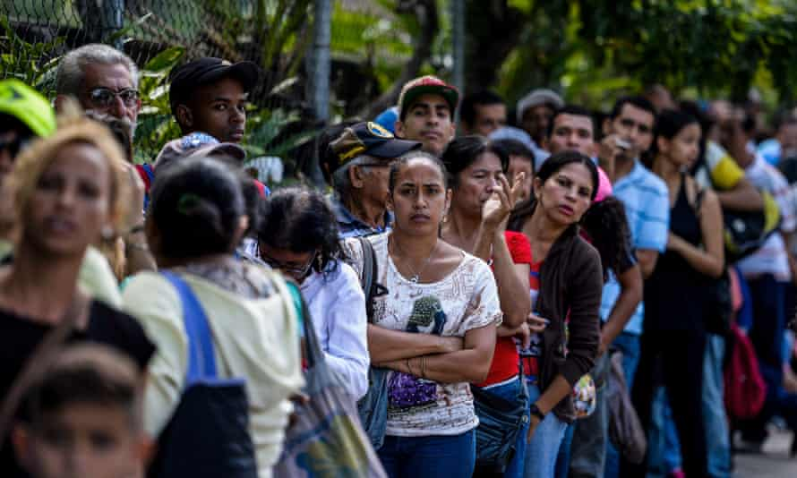 People queue outside a supermarket in Caracas.