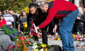 People place flowers in remembrance of Cpl Nathan Cirillo after he was killed by a gunman in Ottawa.