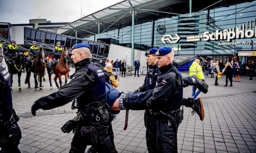 Royal military police remove a protester from the main hall of Schiphol airport.
