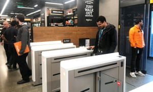 A shopper scans a smartphone app associated with his Amazon account and credit card information to enter the Amazon Go store in Seattle.