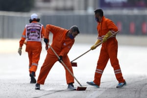 Track marshals sweep the track following the crash.
