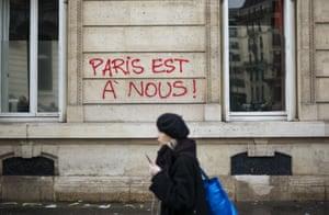 """A woman walks past graffiti reading """"Paris is ours"""", near the Arc de Triomphe"""