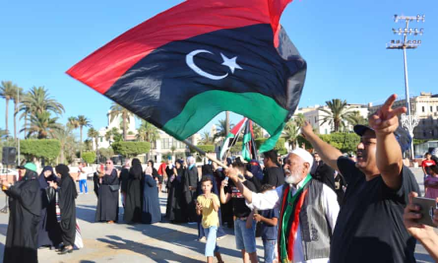 A man carries the flag of Libya during a protest in Tripoli against the president of Egypt, Abdel-Fatah Al-Sisi.