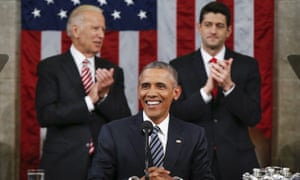 President Barack Obama sits, smiling, behind a microphone.  Behind him Vice President Joe Biden, to the left, and Speaker Paul Ryan, to the right, applaud in front of a large American flag.