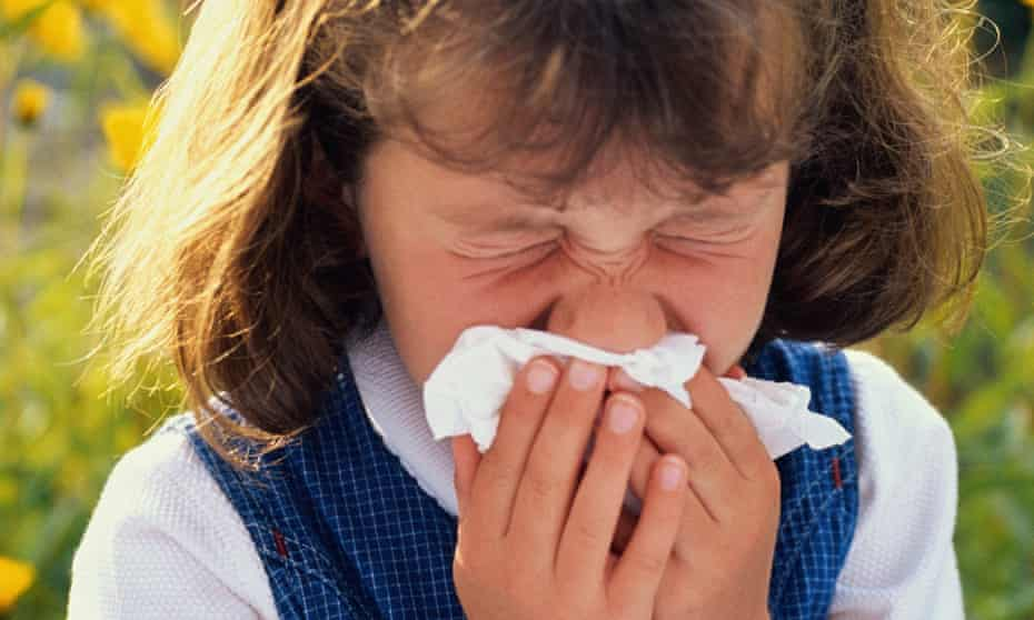 Girl sneezing due to hay fever