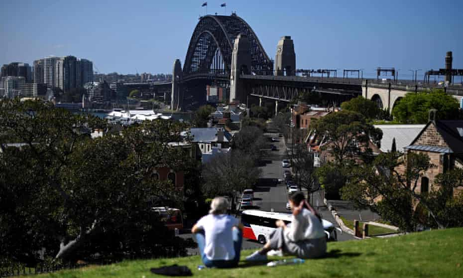 Two women look from a hill at Sydney Harbour