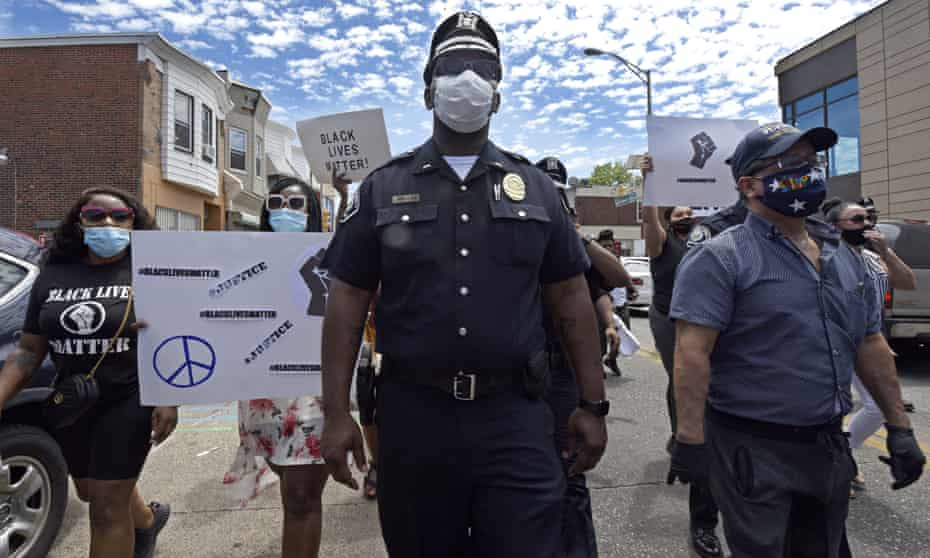 A Camden county police lieutenant marches with protesters in Camden, New Jersey, on 30 May.