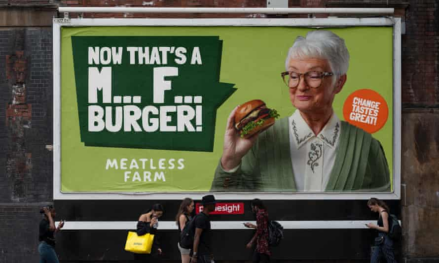 """Advert of a woman holding a burger, strapline says: """"Now that's M*** F*** burger"""""""