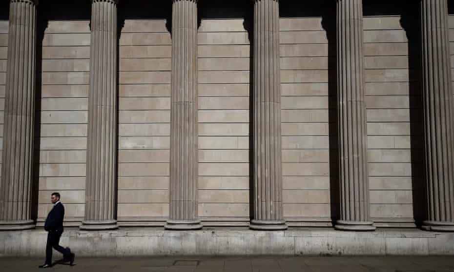 A pedestrian walks past the Bank of England in the City of London.