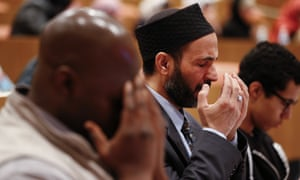 Mohammed Fytahi, of Indianapolis, right, prays during a moment of silence at a Ahmadiyya Muslim Community of Metro Detroit symposium in Dearborn, US. His tribute follows the attacks in Brussels