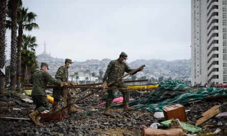 Chilean soldiers clean the debris left by the tsunami.
