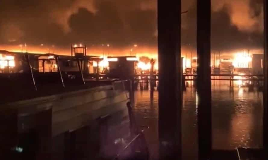 A fire burns on a dock where at least 35 vessels, many of them houseboats, were destroyed by fire.