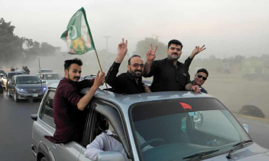 Supporters of Pakistan Democratic Movement in a vehicle with flag