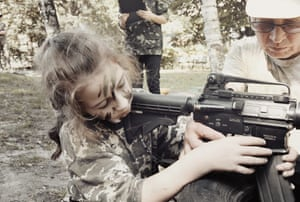 A girl trains with a weapon at a paramilitary youth camp