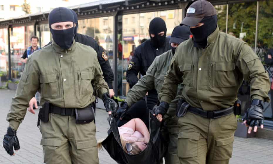 Officers carry a woman away during a protest in Minsk on 19 September.