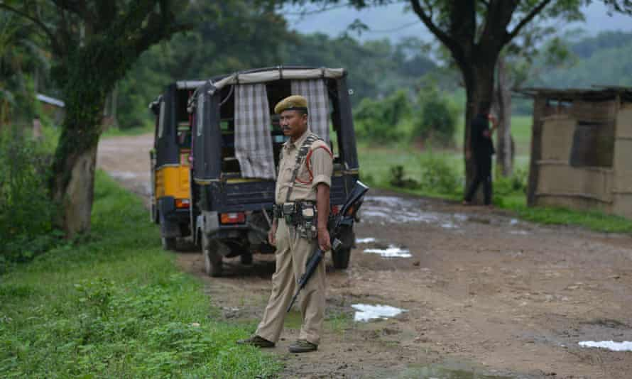 An Indian police officer stands guard near the site in the state of Assam where two men where lynched earlier in July