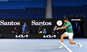 Novak Djokovic plays a backhand from the baseline.
