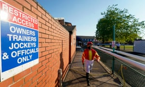 A jockey leaves the weighing room and makes his way to the parade ring at Leicester racecourse.